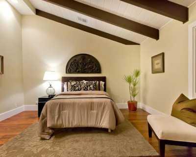 В спальне красивый потолок с балкой